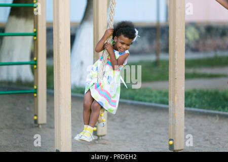 Afrikanische amerikanische Mädchen spielt auf einem Spielplatz. - Stockfoto