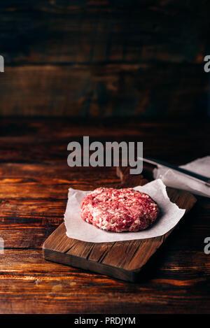 Rohes Rindfleisch Patty für Burger auf Schneidebrett und Wachspapier. Vertikale Ausrichtung und Kopieren. - Stockfoto