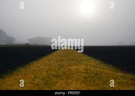 Markierung auf Leere Landebahn mit Gebäuden in einem Nebel. Leer Start- und Landebahn am Flughafen während einer nebligen Morgen. Sunrize über Start- und Landebahn in einem Nebel. Start- und Landebahn mit Yel - Stockfoto