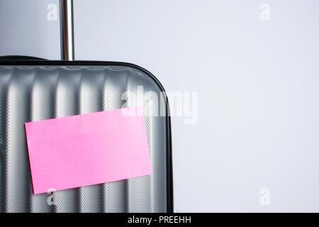 Teil einer grauen Koffer für Reisen mit einem rosa Aufkleber auf einem grauen Hintergrund mit einem Platz unter dem Text - Stockfoto