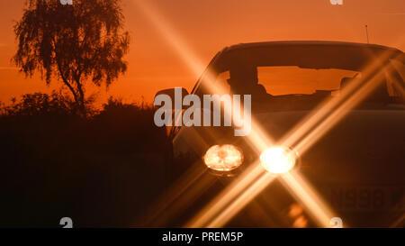 Auto mit Scheinwerfern auf der Landstraße bei Sonnenuntergang york Yorkshire United Kingdom - Stockfoto