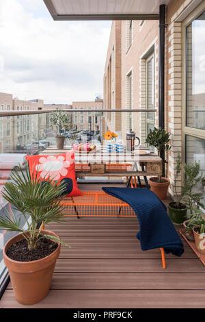 Palette Tisch und Sitzbänke mit hoseplants auf balcont im Norden von London New Build - Stockfoto