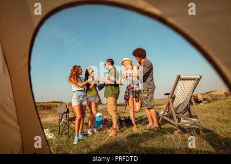 Glückliche junge Freunde genießen Sie einen sonnigen Tag in der Natur. Sie Bierflaschen klirren, lachen und reden gerne zusammen zu sein. - Stockfoto