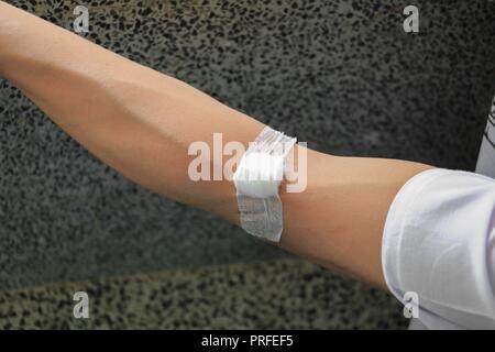 Verband und Gaze auf einem Arm nach einer Blutprobe: Wählen Sie Fokus mit geringer Tiefenschärfe. - Stockfoto