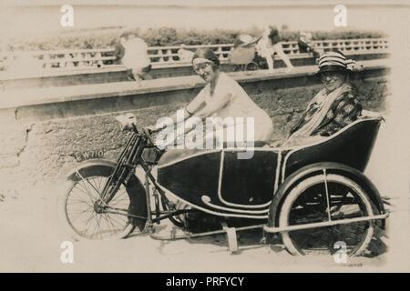 Zwei Damen, die für die Fotografie auf eine AJS Motorrad & Seitenwagen Kombination am Strand posieren am Meer ca. 1914/18 - Stockfoto