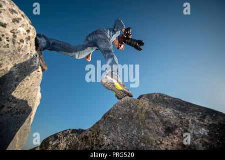 Mann Stepping über Geröll tragen Wanderschuhe und eine Kamera. - Stockfoto