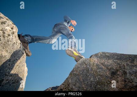 Mann Stepping über Geröll tragen Schuhe. - Stockfoto