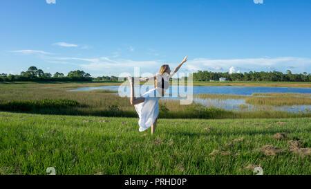Blonde Frau spirituellen Yoga König Tanz ständige Ziehen bug Natarajasana/Dandayamana Dhanurasana Pose in der Natur - Stockfoto