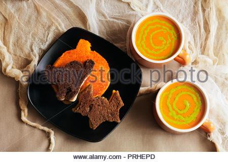 Roggen, Pumpernickel und ornage farbige Cut-out Halloween gegrillter Käse Sandwiches. Tomatensuppe mit Pesto wirbelt in Vintage orange Cups. Zerfetztes Fleck - Stockfoto