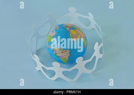 Papier Menschen in einem Kreis um die Erdkugel auf blauem Hintergrund - Begriff der Liebe und der Einheit - Stockfoto