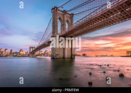 New York, New York, USA, an der Brooklyn Brücke über den East River nach Brooklyn in der Abenddämmerung. - Stockfoto
