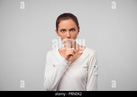 Shh, behalten Sie dieses Geheimnis von jedermann. Portrait von weiblichen stilvolle Frau, psst Geste mit dem Zeigefinger über Mund, Lippen, Falten, q Halten - Stockfoto