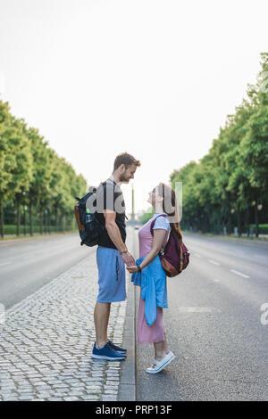 Seitenansicht des Paar Hände halten und an einander auf der Straße in Berlin, Deutschland - Stockfoto
