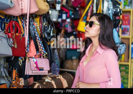 Junge Frau auswählen und Einkaufen Handtasche in Store - Stockfoto