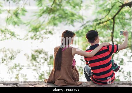 Junges Paar ein selfie auf Ihrem Mobiltelefon am Ufer der Schwert See bei Sonnenuntergang. Romantischer nachmittag Outing. Üppiges Grün und See - Stockfoto