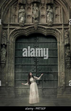 Frau in Weiß vor der großen Tür der Villa. - Stockfoto