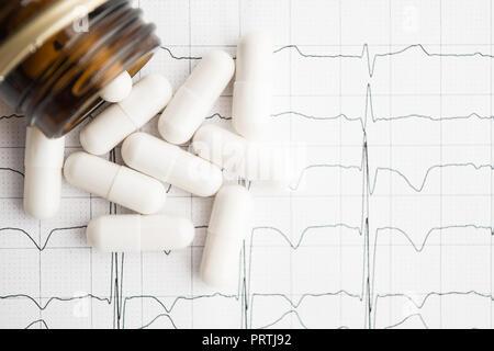 Weiße Pillen in jar auf Papier Elektrokardiogramm mit Kopie Raum, Flach, Ansicht von oben - Stockfoto