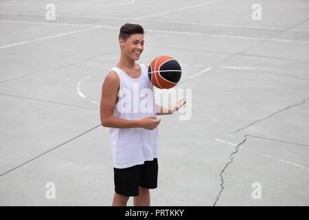 Männliche Teenager basketball Player auf basketballplatz Werfen und Fangen ball - Stockfoto