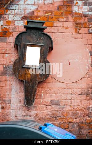 Toter Spiegel in ein Musik Instrument förmigen Rahmen hängt an rot gestrichenen Wand. Vertikale. Müllcontainer im Vordergrund - Stockfoto