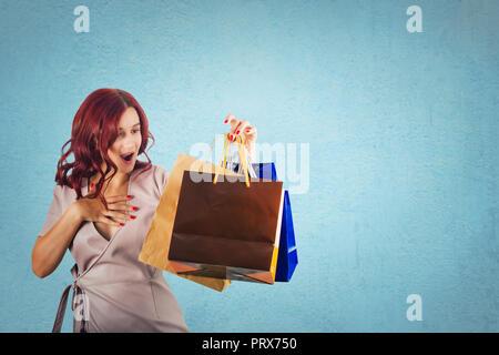 Überrascht rothaarige junge Frau die Hand auf die Brust, während Sie einkaufstaschen über blauen Hintergrund mit Kopie Raum isoliert. - Stockfoto