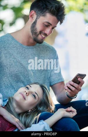 Mann mit einem Smartphone, während Frau sich auf seinen Schoß. - Stockfoto
