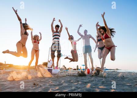 Eine Gruppe von Freunden eine Party am Strand bei Sonnenuntergang Zeit - Stockfoto