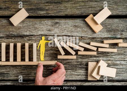 Konzeptionelle Nahaufnahme der Hand eines Mannes mit Unterstützung durch eine stabile Plattform für ein Papier Mann stoppen Der Zusammenbruch von Domino Effekt verursacht. - Stockfoto