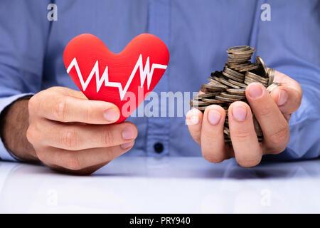 Close-up In eines Mannes Hand halten roten Herzen mit Pulsfrequenz und goldenen Münzen - Stockfoto