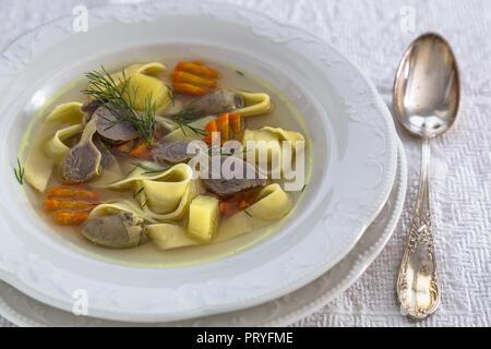 Hühnersuppe mit Nudeln und Gemüse in eine weiße Platte, Ansicht schließen - Stockfoto