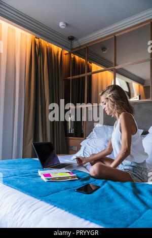 Frau sitzt auf dem Bett, mit laptop - Stockfoto