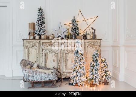 Geschmückter Weihnachtsbaum auf hölzerne Kommode Kommode Kommode in weiße Interieur mit künstlichen Blumen, Girlanden und Spielzeug - Stockfoto