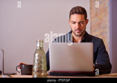 Eine ernsthafte hübscher junger Geschäftsmann trinken Kaffee im Büro. - Stockfoto