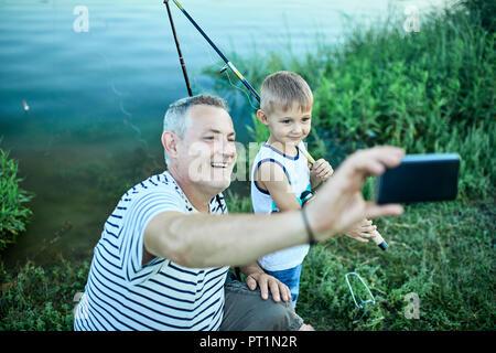 Großvater und Enkel unter selfie mit Smartphone am Seeufer - Stockfoto