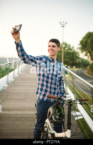 Lächelnden jungen Mann mit Klapprad auf einer Brücke ein selfie - Stockfoto