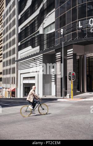 Reifer Mann reiten Fahrrad in der Stadt - Stockfoto