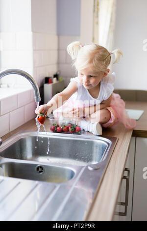 Kleines Mädchen sass auf der Arbeitsplatte in der Küche Waschmaschine Erdbeeren - Stockfoto