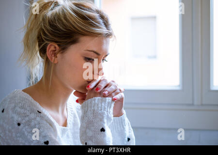 Hoffnungslose junge Mädchen beten weiter, um das Fenster - Stockfoto