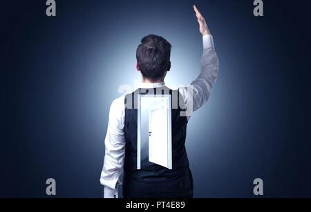 Junge Unternehmer stehen und denken mit einer offenen Tür auf seinem Rücken - Stockfoto