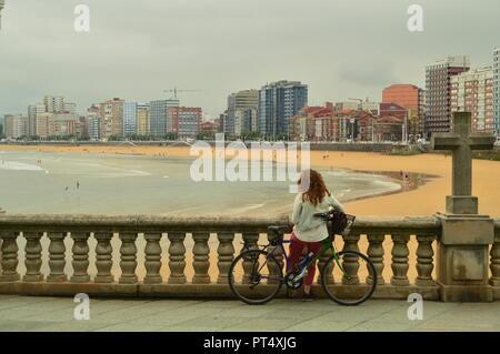 Radfahrer Frau genießen Sie die Aussicht auf die Bucht mit einem Kreuz neben Ihr am Strand von San Lorenzo in Gijon. Reisen, Urlaub, Städte. Juli 31, 2018. Gij - Stockfoto