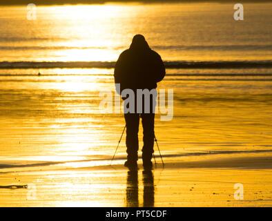 Langen Felsformation, Cornwall, UK. 7. Oktober 2018. UK Wetter. Ein Fotograf der Erfassung der Sonnenaufgang über Marazion heute Morgen. Foto: Simon Maycock/Alamy leben Nachrichten - Stockfoto