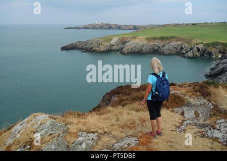 Einsame Frau Wanderer in Richtung Point Lynas Leuchtturm, von der Landspitze über Porthyrychen auf der Insel Anglesey Coastal Path, Wales, UK. - Stockfoto