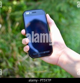 Reflexion der männlichen Teenager jungen Gesicht auf CAT S41 robustes Smartphone mobile Handy in der Hand gehalten, auf der CES, Las Vegas, USA empfohlene - Stockfoto