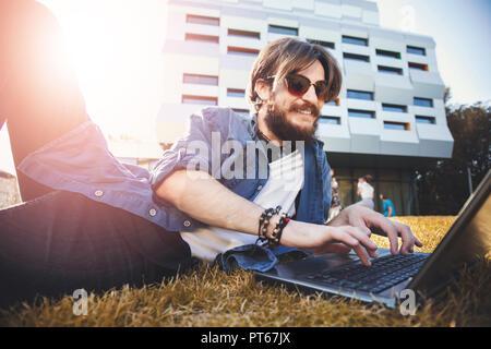 Schöne bärtige student Mann mit Brille in der Nähe der Universität liegen und Studieren mit dem Laptop, Konzeption Studium - Stockfoto