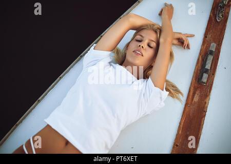 Attraktive junge Frau in einem Bikini Bottom und Shirt suntanning beim Liegen mit ihren Augen auf dem Deck einer Yacht geschlossen - Stockfoto