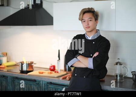 Asiatisch Kochen in der Küche bereitet Essen in einer cook Anzug - Stockfoto