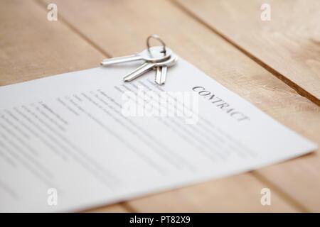 Tasten und Vertrag Papier auf einem Holztisch - Stockfoto