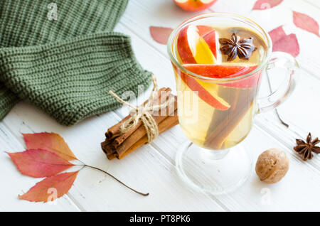 Herbst Glühwein oder Glühwein auf Weißwein mit Rum, Apple und Gewürze Zimtstangen, Sternanis, Muskatnuss, Kardamom und Nelken auf weißem Holz- - Stockfoto