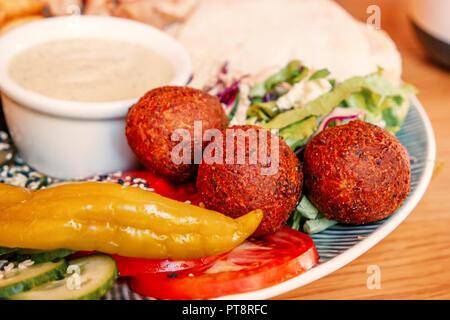 Nahaufnahme des Falafel, Fladenbrot, Gemüse und Hummus auf Platte, traditionellen arabischen und israelischen Snack - Stockfoto