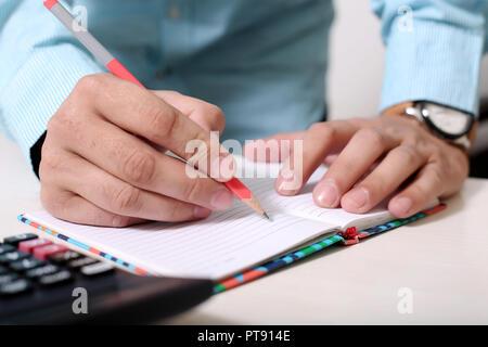 Mann mit Bleistift in der Hand mit Notebook und Rechner auf dem Tisch. - Stockfoto