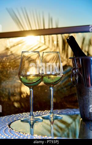 Zwei Gläser der weißen kalten Wein auf ein Glas Tisch auf dem Balkon in den Strahlen der untergehenden Sonne vor dem Hintergrund der Blätter der Palmen. - Stockfoto